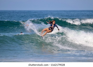Huntington Beach, CA / USA - August 1, 2018: Professional French surfer Pauline Ado surfing on the north side of the Huntington Beach Pier in Huntington Beach California