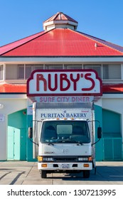Huntington Beach, CA / USA - February 7, 2019: The Puritan Bakery truck delivering to Ruby's Surf City Diner on the Huntington Beach Pier