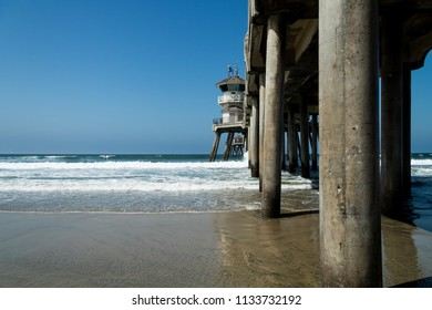 Huntington Beach, CA / USA - July 13, 2018: People on the south side of the Huntington Beach Pier watching surfers in the water and enjoying a summer day in Southern California