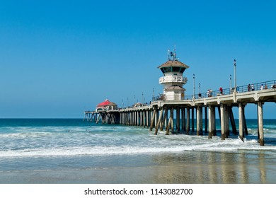 Huntington Beach, CA / USA - July 13, 2018: People enjoying the beach and surfing on a sunny summer day at the Huntington Beach Pier