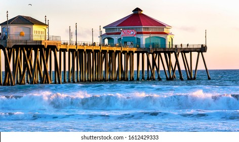 Huntington Beach, CA / USA - March 27, 2019: Ocean waves and the end of the Huntington Beach pier at sunset. Ruby's Diner is located at the very tip of the pier and attracts visitors to the area.