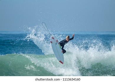 Huntington Beach, CA / USA - October 6, 2017: Surfer Clay Pfaendler surfing off the coast of Huntington Beach California on a DMA Surfboard
