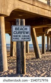Huntington Beach, CA / USA - October 22, 2019: Beach curfew sign at the Huntington Beach Pier