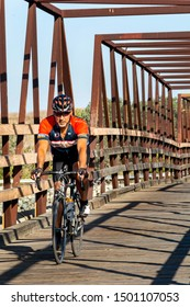 Huntington Beach, CA / USA - Sept 10, 2019: Cyclist crosses the wooden footbridge over the Santa Ana River. The bridge is popular with runners, bicyclists and people walking their dogs.