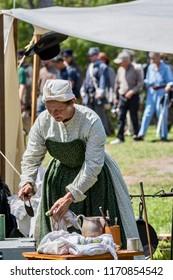 Huntington Beach, CA / USA - September 1, 2018: a woman dressed in civil war era clothing cutting vegetables during a reenactment