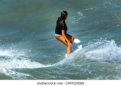 Huntington Beach, Calif. / USA - Sept 7, 2019: Closeup of a tan young woman surfing near the pier on a hot summer afternoon.