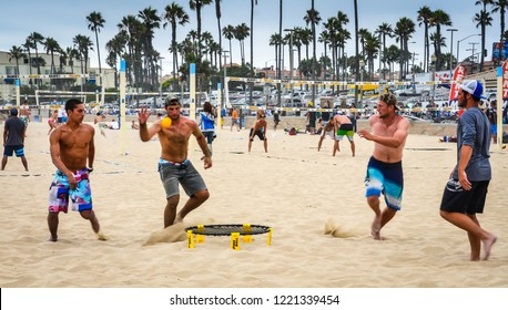 Huntington Beach, California / USA - July 27, 2013: Young men playing a game of Spikeball on the sand.