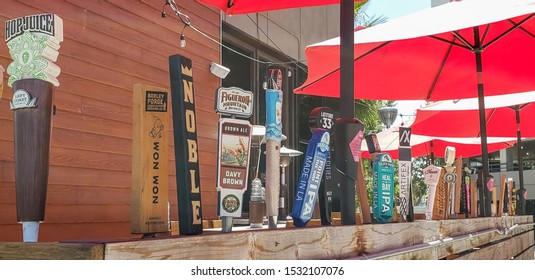 Huntington Beach, California/United States - 09/04/2019: Several beer tap handles featuring various beer brands, as decoration on a patio of a restaurant.