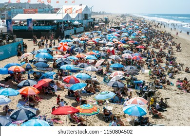 Huntington Beach, CA/USA - August 5, 2018: A view from the Huntington Beach Pier shows beach umbrellas and surfing fans filling the beach for the 2018 Vans U.S. Open of Surfing.