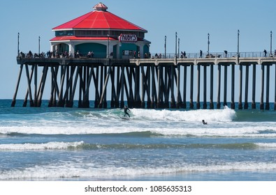 HUNTINGTON BEACH, CA/U.S.A. - MARCH 26, 2018: A photo of a surfer in a wetsuit catching a wave in front of Ruby's restaurant on the pier at Huntington Beach.