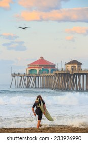 The Huntington Beach pier at sunrise, CA with surfer