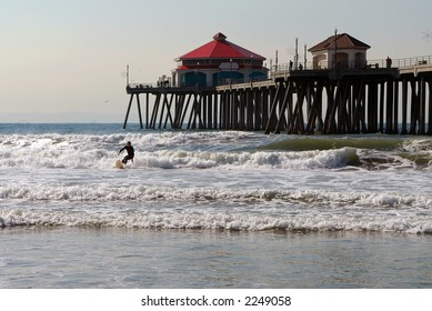 Huntington Beach Pier with surfer in foreground.