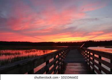 Huntington Beach State ParkDramatic sunset over the expansive salt marsh. Scenic view with wooden boardwalk and amazing colors after sunset sky reflects in a calm water. Murrels Inlet, SC, USA.