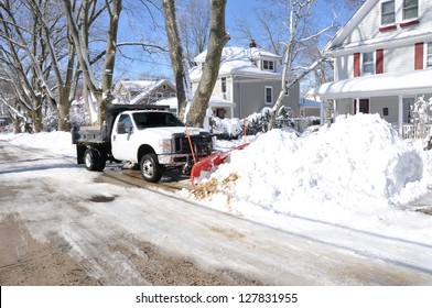 HUNTINGTON, NEW YORK - FEB 10: Plow truck clearing snow on suburban street after Feb 8 winter blizzard hit north east region of USA dumping at least 2 feet of snow in Huntington, Feb 10, 2013.