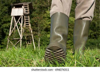 A huntsman walks through the meadow at his hunting pulpit with green rubber boots.