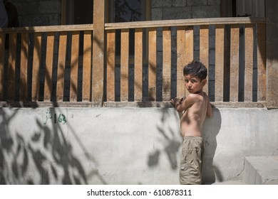 HUNZA VALLEY, PAKISTAN. JULY 20, 2013 : Portrait of an unidentified young boy standing in front of balcony.