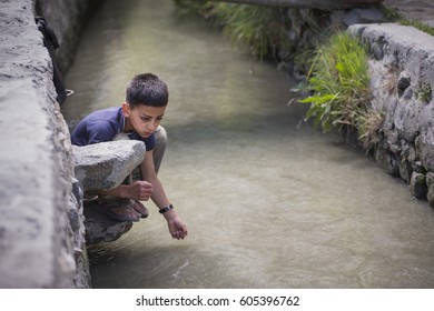 HUNZA VALLEY, PAKISTAN. JUN 19, 2013 : An unidentified child playing in the canal. KARIMABAD, HUNZA VALLEY, PAKISTAN