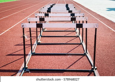 A hurdle race on red running in stadium track