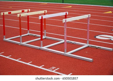hurdles in a row on red sport field