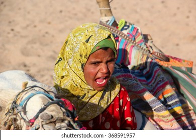 HURGHADA, EGYPT - Apr 24 2015: The young girl-cameleer from Bedouin village in Sahara desert with her camel, shouting inviting tourists, Egypt, HURGHADA on Apr 24, 2015.
