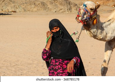 HURGHADA, EGYPT - Apr 24 2015: The old woman-cameleer from Bedouin village in Sahara desert with her camel, Egypt, HURGHADA on Apr 24, 2015.
