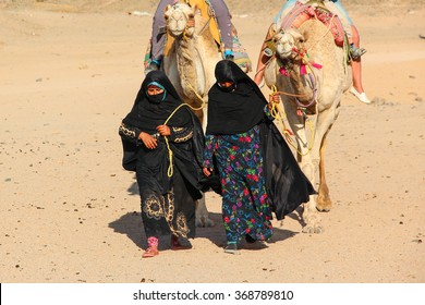 HURGHADA, EGYPT - Apr 24 2015: The old and young women-cameleers from Bedouin village in Sahara desert with their camels, Egypt, HURGHADA on Apr 24, 2015.