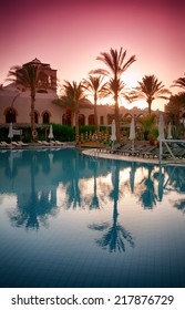 HURGHADA (EGYPT) - CIRCA JUNE 2013 - Still Water on Resort Swimming Pool Surrounded by Palm Trees at Sunrise or Sunset