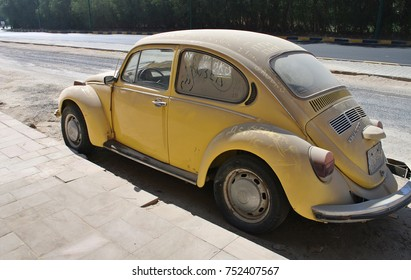 HURGHADA, EGYPT - FEBRUARY 09, 2017: A vintage german motor car Volkswagen Beetle in yellow colour parked in a street. Dirty car with ukrainian and russian political words written on it.