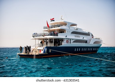 Hurghada, Egypt - February 24, 2017: white ship or yacht, modern motor boat and group of people, scuba divers, in wetsuits, snorkels in blue sea on summer day on clear sky. Snorkeling activity