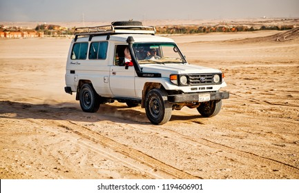 Hurghada, Egypt - February 26, 2017: white toyota, land cruiser, japanese car or jeep, offroad vehicle, driving on desert, sand dunes surface on blue sky background. Recreational offroading