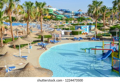 Hurghada, Egypt - May 15th, 2018: From above view of aquapark sliders, pool, deck chairs, sun umbrellas. Concept of sea resort.