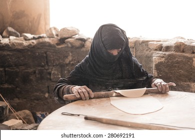 HURGHADA, EGYPT - MAY 2015 - Old Arab woman prepares bread in a Bedouin village