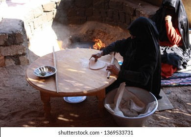 Hurghada, Egypt - November 2012. Bedouine woman in traditional costume cooking a bread on the fire