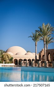 HURGHADA, EGYPT - NOVEMBER 21, 2006: A 5-star hotel resort with the pool, palm trees and restaurant in view against a cloudless blue sky providing copy space.