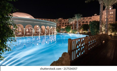 HURGHADA, EGYPT - NOVEMBER 21, 2006: A 5-star hotel resort restaurant by the pool with diners in view but made anonymous through motion blur on this long exposure night scene.