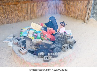 HURGHADA, EGYPT - OCTOBER 5, 2014: The Bedouin woman cooks the bread in the outdoor oven, sitting on the sand, on October 5 in Hurghada.