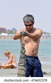 HURGHADA,EGYPT - SEPTEMBER 25,2010:a Man builds a sand castle on the beach