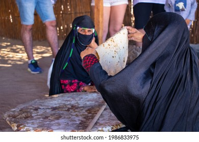 Hurghada,Egypt,13.5.2021- Bedouin's woman making traditional bread called pita on open fire for tourists as a present for their coming. Second woman is helping her with preparation.