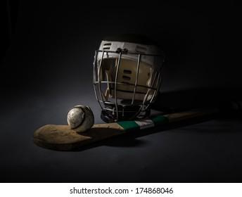 Hurling Equipment From Above. a studio shot of a hurling stick, ball, and helmet. single light illumination