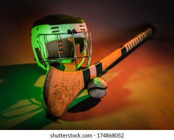 Hurling Equipment Color. a studio shot of a hurling stick, ball, and helmet in colorful green and orange light. irish