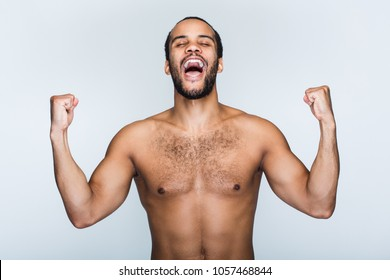 Hurray and cheers! Portrait of handsome shirtless young black man looking excited while standing against white background