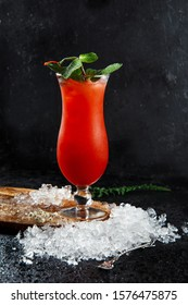 Hurricane cocktail, orange red, with a sprig of mint and a flower