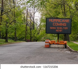 Hurricane Coming Seek Shelter warning information sign on trailer with LED face on suburban street lined with trees