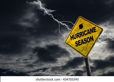 Hurricane season with symbol sign against a stormy background and copy space. Dirty and angled sign adds to the drama.