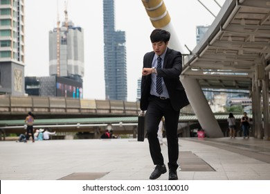 Hurry Asian businessman running and looking at watch to check time on city walk in rush hour. Young man late for train transportation, work, meeting. Office life and business competition.