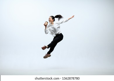 Hurry up to get your coffee. Happy woman working at office, jumping and dancing in casual clothes or suit isolated on white studio background. Business, start-up, working open-space concept.