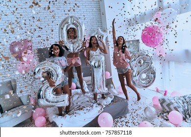 Hurry up to make a wish! Top view of four attractive young smiling women in pajamas holding silver colored balloons while standing in the bedroom with confetti flying everywhere