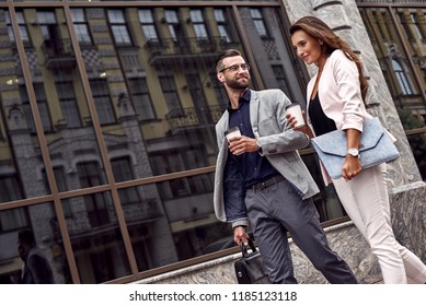 Hurry for meeting. Two young business people walking outside on the city street drinking hot coffee talking smiling joyful close-up
