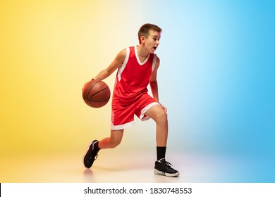 Hurry up. Portrait of young basketball player in uniform on gradient studio background. Teenager confident practicing with ball. Concept of sport, movement, healthy lifestyle, ad, action, motion.
