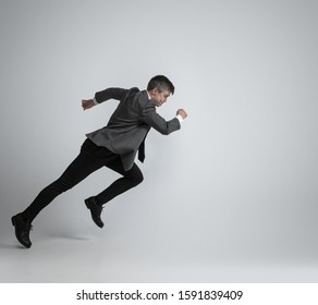 Hurry up, you're wild and young. Caucasian man in office clothes running like a professional sportsman on grey background. Businessman training in motion, action. Sport, healthy lifestyle concept.